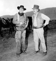 THE SEARCHERS (1955) - Ward Bond & John Wayne take a cigarette break between scenes in Monument Valley - Directed by John Ford - Warner Bros. - Publicity Still.