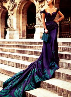 This rich purple color and long train with a blue - green design makes me think of peacocks.  Such a bold and beautiful dress.