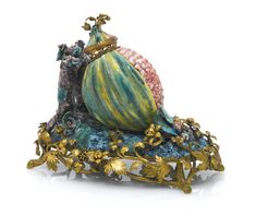 A very rare gilt-bronze mounted pomegranate pot-pourri, circa 1745-50 probably Chantilly, naturalistically modelled and painted as a ripe green pomegranate with a hinged cover with a pierced gallery, beside two small tree-stumps issuing flowers, resting upon a rockwork base applied with leaves and flower buds, raised on a later foliate mount.