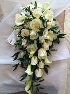 Classic White shower brides bouquet wedding flowers roses, calla lilies, freesia, Veronica trailing foliage. Lily White Florist West Midlands wedding florist