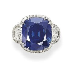 A UNIQUE SAPPHIRE AND DIAMOND RING - Set with a cushion-shaped sapphire weighing 42.28 carats, to the half-moon diamond shoulders, mounted in 18k white gold. Price realized $3,458,420