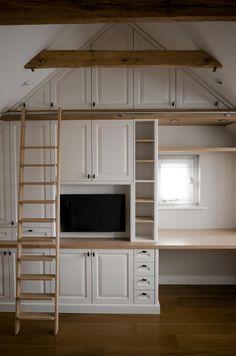Kastenwand nok vullend onder een schuin dak in jaren 30 stijl. Voorzien van bossing paneel fronten en een bibliotheek ladder