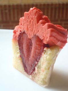 Delicious vanilla cupcake with a strawberry inside and strawberry frosting