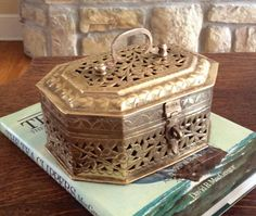 Beautiful large solid brass vintage cricket box for holding keepsakes. This one is solid brass! Great for tv remote on coffee table, bookshelf decor, bathroom, or vanity decor. Octagon shape with a floral filigree pattern on top & sides. Hinged lid with handle & front decorative clasp. Black felt on bottom to protect furniture from scratches. In very good vintage condition. Such a versatile home decor item. Several cricket boxes sold separately in shop.  Measures 8 x 6 x 3.75 height  ...