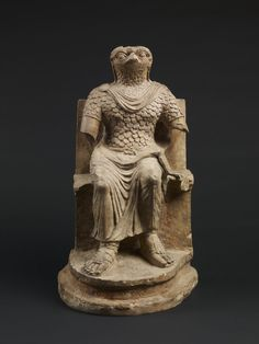 Limestone seated figure of Horus wearing Roman military costume; traces of paint; arms lost. The falcon head is rendered with careful attention to the feathering around the face; the eyes are human and the pupils are incised.  Egypt