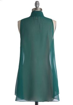 When you don this silky chiffon top blanketed with a deep hunter-green hue, everyone around you can't help but say hello. Composed of sheer chiffon, this solid top features a slight high-low hem and a tied collar. For a look that will take wing, layer it over an ivory tank and pair it with a high-waisted skirt, vintage-inspired heels, and a crochet cardigan. Sheer Chiffon, Chiffon Tops, Hijab Fashion, Fashion Dresses, Hijab Style Tutorial, Black Lace Blouse, Plain Dress, Short Tops, Crochet Cardigan