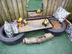 Eyfs small world outside construction area. Very easy to make using two tyres a garden planting tray, gravel and a couple of diggers. The cushions are wipe able pvc great for using outside.