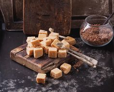 Sweet creamy fudge candies - Rustic wooden boards with fudge candy glass sugar bowl, served with sugar cubes over dark background