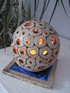 světelná koule Světelná koule o průměru 13 cm, vyrobená ze šamotové hlíny a glazovaná šedomodrou glazurou. Pod koulí je čtvercový kachlík zalitý modrým sklem a také glazovaný šedomodrou glazurou.