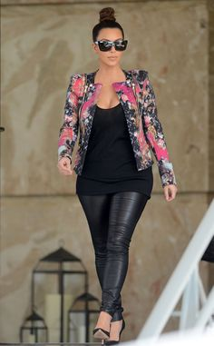Kim Kardashian tops her sexy black leather leggings with a funky floral print jacket. A sleek top bun and oversized shades finish off her look.