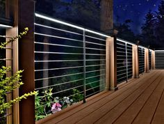 Feeney Cable Rail with posts matching decking (Ipe, it looks like).  Integrated lighting system in the DesignRail by Feeney.