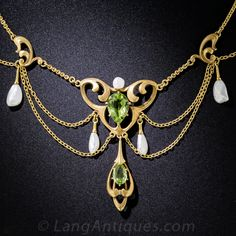 A splendid and artsy original Art Nouveau swag necklace centering on a pair of glistening lime green pear-shape peridots presented in curvaceous lightly textured golden frames. The central gemstones are enhanced with lustrous white freshwater pearls. A fanciful and feminine jewel lovingly crafted in 16K (pendant) and 18K (chain) gold - circa 1900.