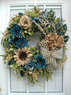 """Artificial new handmade floral door / wall wreath Approx. measurements are 24"""" wide x 26"""" long x 6-7"""" deep made on a grapevine wreath base.  """"Teal Blue and Brown"""" This design would work for fall and even all year long. Wispy dahlias and budding roses in shades of gorgeous teal blue are combined with light brown burlap hydrangea, sunflower and rose. I accented the design with tiny clusters of teal flowers and creamy tan seeded stems. Shooting up from the hydrangea are silk pheasant feathers…"""