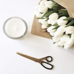 Fresh white tulips wrapped in brown paper and gold scissors | onlinestylist on Instagram |