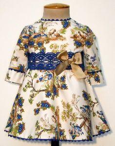 Vestido para bebe niña de toilé en tonos azules y manga francesa, adornado con encaje de bolillos azul y piquillo. Talle a la cintura con la falda a capa. Forrado.