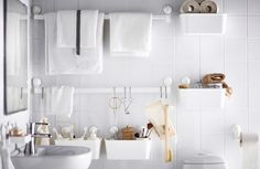 Different white plastic organisers hangs with the help of suctions-cups on the a white tiled bathroom wall