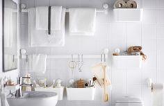 Diferentes organizadores de pared blancos colgados con ventosas en una pared de baño con baldosas blancas