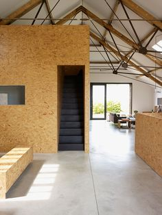 Chipboard and black painted stairs and ceiling rafters. Ochre Barn by Carl Turner Architects.