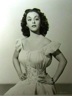 Estelita Rodriguez, Cuban born actress in off the shoulder dress and wide waist cinching cummerbund, 1950s, vintage south of the border fashion