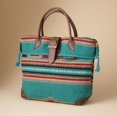 """Timpanogos Travel Bag Named after a magestic mountain, our bag big enough for a weekend combines serape-striped wool with a wool fabric bottom, handles and buckled closure. Nylon lining with two full-length zip pockets. Made in the USA. 19""""W x 6""""D x 13""""H.  $248"""