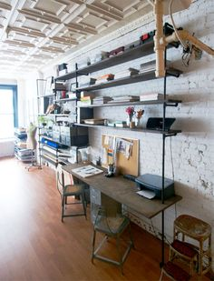 A much larger version of the pipe and plywood shelves, complete with a desk.