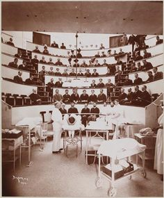 Hospitals, Roosevelt Hospital, Operating Theatre.   Date:  1900    The operating theatre at Roosevelt Hospital on 59th Street and Columbus Avenue. Medical students look on while Dr. McBurney speaks. A nurse stands in the wings Museum of the City of New York