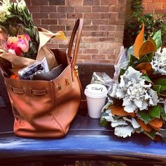 Love the fresh flowers, coffee + tan leather bag. Perfect Saturday morning.