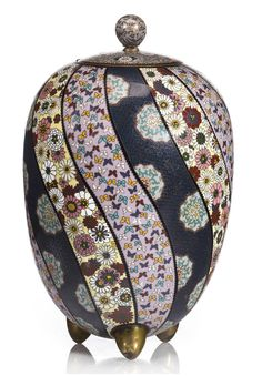 A cloisonné enamel ovoid container Meiji period (late 19th century) The inverted egg-shaped body raised on three tapering gilt supports and decorated in brightly colored enamels with twelve undulating vertical bands of floral roundels, millefleur or butterfly pattern, the fitted lid featuring chrysanthemum and tendrils below a finial with miniature phoenix and flowering paulownia