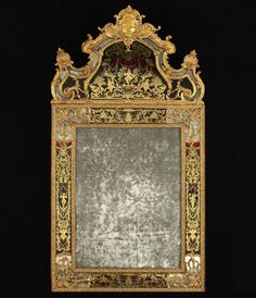 """A Louis XIV Giltwood and Eglomised Mirror with pediment topped by a female mask part of a cartridge with shell decor scroll foliage, the background and the borders decorated with chinoiserie in gold, red and blue on black, the spandrels trimmed with foliage, an inked registration visible on the back of the mirror, """"Joannes Joanez or guardian ... / in Paris"""" - Height : 181 cm (71 1/4 in.), Width: 98 cm (38 1/2 in.)"""