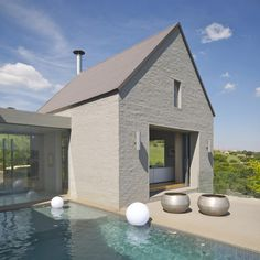 House Bezuidenhout - formal lounge opens onto the pool deck, which becomes an extension of the living space. The steeply pitched roof ventures a modern take on barn style architecture