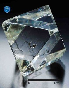 Diamond - Russia Udachnaya-Vostochnaya Trubka, Respublika Sakha, Sibir' 53.05 carats Transparent almost perfect 53.05 carat octahedron with smooth and flat faces, with some slightly modified terminations and inclusions (of flattened sulfide crystals, probably pyrrhotite+pentlandite) in its center. The latter are reflected 4 times thanks to a kaleidoscope effect on the faces. Unlike most diamonds, this one has almost not been dissolved by the kimberlite which must have risen very fast to…