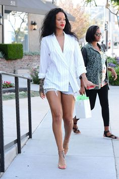 Rihanna looks amazing! Love her style. Rihanna tip toes between a masculine and feminine look by adding an oversized shirt and sexy ankle-strap sandals to her cutoff shorts.
