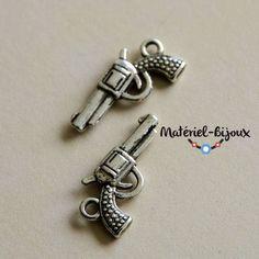 Les petites breloques en forme de revolver en métal et couleur argent antique.