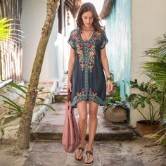 FOLKLORIQUE DRESS -- Flowing and flattering, this beautiful, pull-on dress features embroidery all around and delicate trim details at…