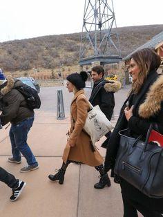 Emma Roberts winter camel coat, pompom beanie, combat boots, polka dots celebrity street style | seen in Park City, Utah on Jan. 20, 2018.