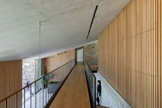 A concrete staircase at the centre of the house connects the bedroom level with the kitchen, dining and living space below. This room is also linked to the mezzanine above by a staircase featuring cantilevered treads that extend out from a concrete wall. Concrete Bench, Concrete Steps, Exposed Concrete, Concrete Staircase, Eco Construction, Ligne D Horizon, Hidden Spaces, Wood Pergola, Dry Stone