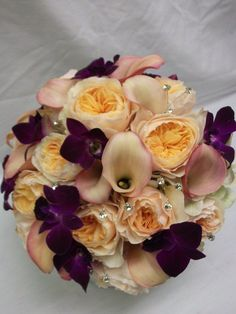 Bouquet made of peach/pink calla lilies, purple dendrobium orchids, white hydrangea, and peach David Austin roses.