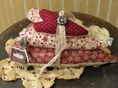 This trio of burgundy and cream floral primitive hearts is secured by an antique lace ribbon and features a key and charm which has a vintage picture and the words Family Love.