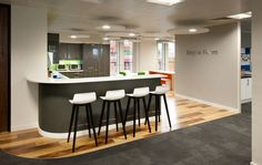 Workplace kitchen including breakfast bar and stools for chatting over lunch
