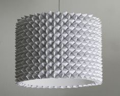 Lampshade made using origami fortune tellers (the ones you used to make at school). Arrange 4 ft's in a square, then glue a fifth on to the centre of them to lock them together. Repeat going outwards to achieve whatever surface area / shapes you like.