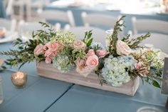 Another classic element of an elegant rustic wedding, the wood box centerpieces. These are simply delightful! We love the light blue and blush pink flowers with added greenery. It's a favorite wedding Flower Box Centerpiece, Blue Centerpieces, Rustic Wedding Centerpieces, Wedding Table Centerpieces, Table Flowers, Wedding Decorations, Centerpiece Ideas, Rustic Flower Arrangements, Quinceanera Centerpieces