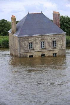 """Si chiama """"La maison dans la Loire"""", la casa sulla Loira, una delle nove installazioni che compongono la mostra """"Estuaire"""", allestita sull'estuario della Loira. Realizzata da Jean-Luc Courcoult l'opera fa galleggiare un'abitazione, dalle sembianze di un castello, nelle acque del fiume francese    (afp)"""