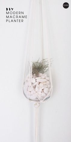 Modern macrame planter. How to make this using venetian blind cord, a stemless wineglass, some decorative rocks and an air plant. Super easy to make with just four things.