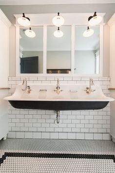 Art Deco style bathroom with hexagon tiles, three mirrors and taps, large sink white metro tile walls. Black and white retro sink. | French Bedroom Company
