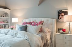 Gorgeous girl's room with white velvet tufted wingback headboard on queen bed layered with white striped bed linens accented with pink embroidered pillow shams, pink and gray floral pillows, white striped pillows and a small gray sequin pillow.