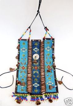 "Well made Plains Indian breast plate crafted between 1880-1900. Fully beaded in three sections with bone beads connecting each section. It is adorned with old trade beads and small bells; the bottom made of trade bead tassels with cowrie shells at the botton. The thick leather backing is still fairly pliable; measures 21"" x 11"""