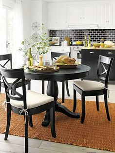 Black table and chairs with white cushions