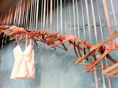 i like the wooden hangers... could be twigs or skinny wood pieces over a painted canvas background