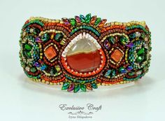 """Colorful and unique bead embroidered bracelet """"Firebird"""" made with Mookaite cabochon, Swarovski crystals, red Agate cabochons and Japanese seed beads."""