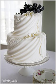 Classic black & white cake, draped front with piped design between the drapes.  With Calla Lilies
